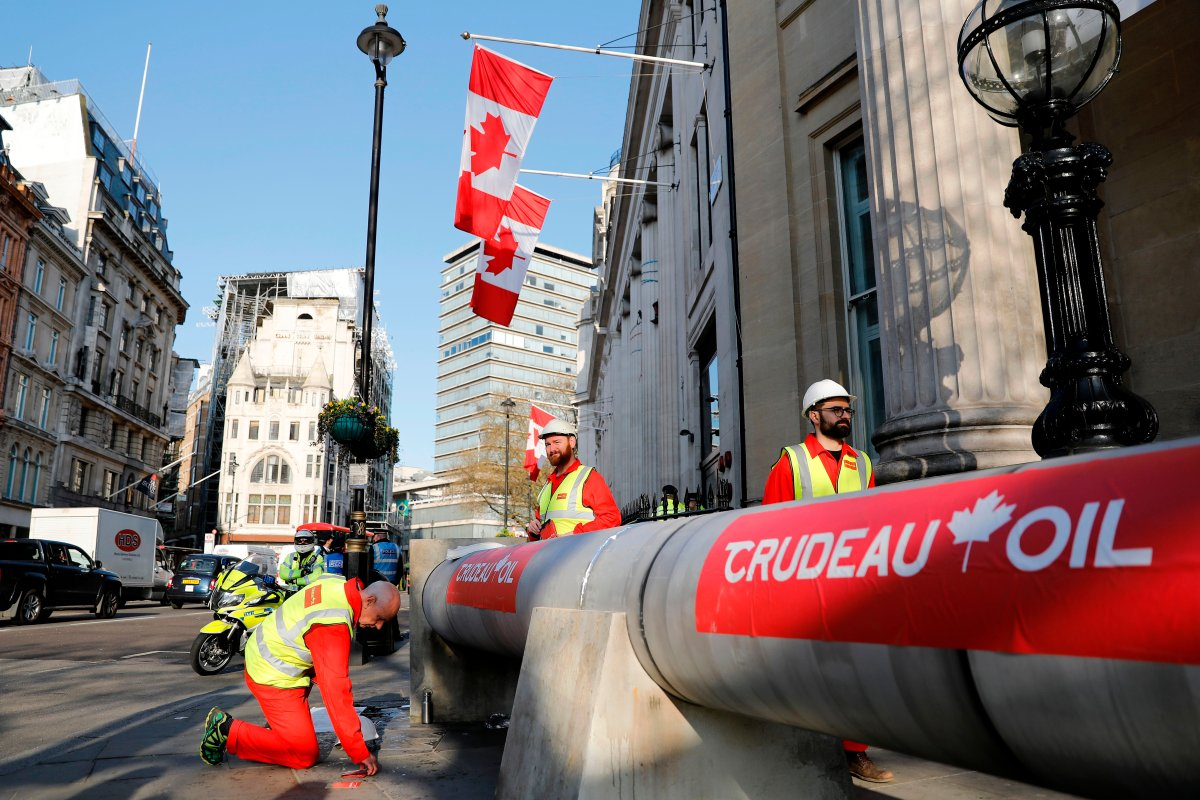 Demonstrators use a mock oil pipeline to block the entrance to the Canadian Embassy in central London on April 18, to protest the Trans Mountain pipeline project.