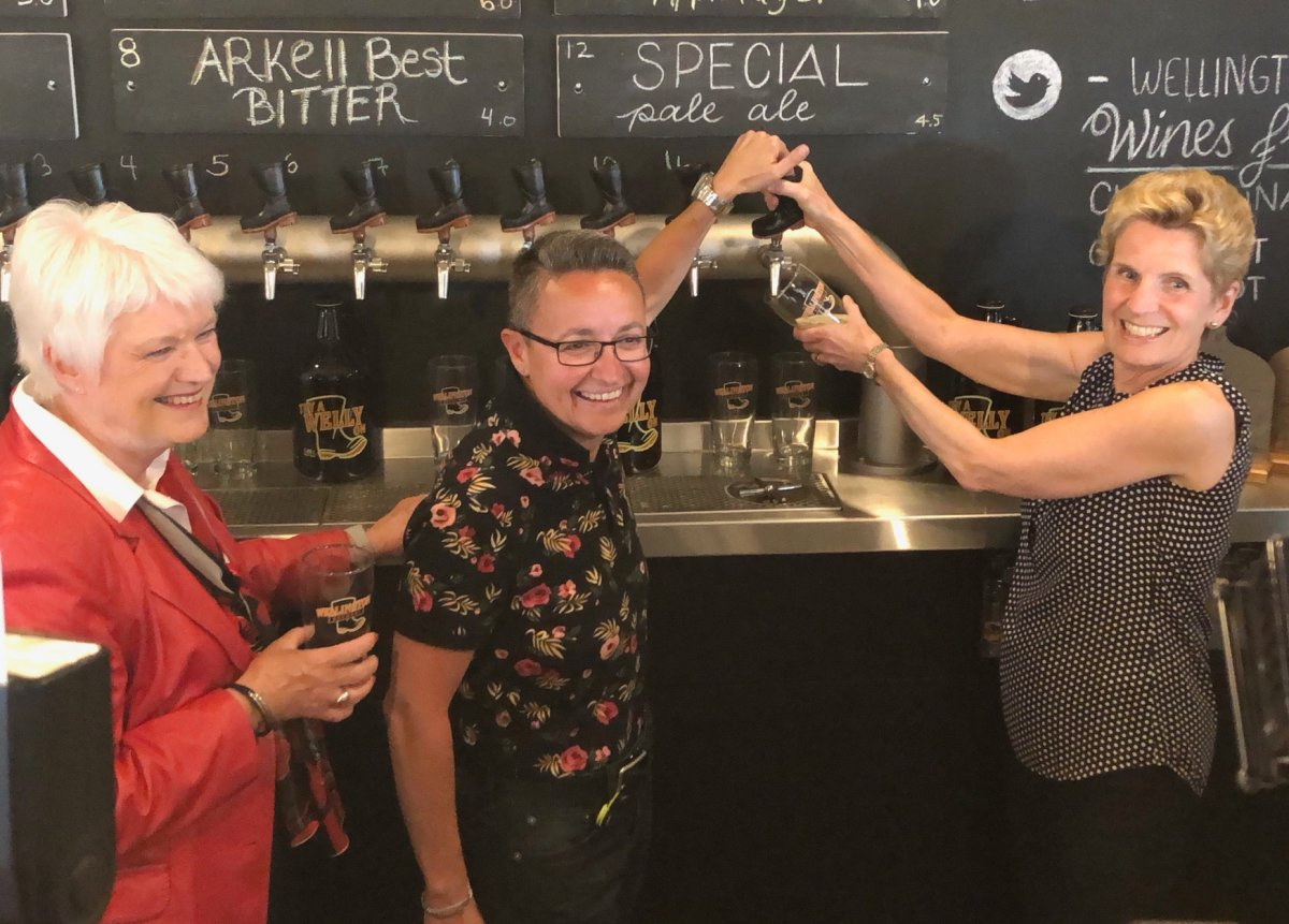 Liberal candidate for Guelph, Sly Castaldi, pours a beer with Ontario party leader Kathleen Wynne and outgoing MPP Liz Sandals during a campaign stop in Guelph.