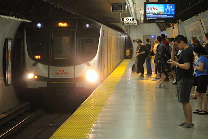 Passengers wait to board a southbound TTC Line 1 subway train.