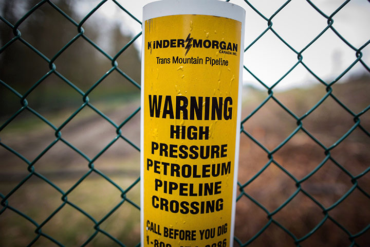 A sign warning of an underground petroleum pipeline is seen on a fence at Kinder Morgan's facility where work is being conducted in preparation for the expansion of the Trans Mountain Pipeline, in Burnaby, B.C., on Monday April 9, 2018.