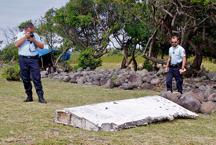 In this July 29, 2015 file photo, French police officers look over a piece of debris from a plane in Saint-Andre, Reunion Island.