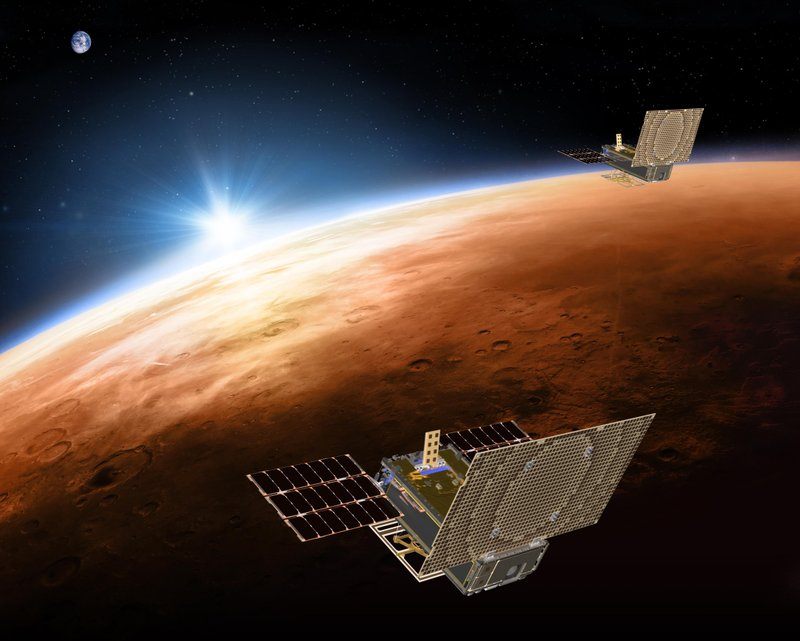 None This illustration made available by NASA on March 29, 2018 shows the twin Mars Cube One (MarCO) spacecraft flying over Mars with Earth and the sun in the distance. The MarCOs will be the first CubeSats - a kind of modular, mini-satellite - flown into deep space. They're designed to fly along behind NASA's InSight lander on its cruise to Mars.
