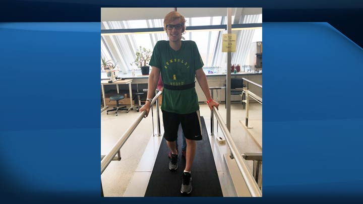Xavier LaBelle's mother Tanya and the Humboldt Broncos bus crash survivor taking part in his physiotherapy treatment in Saskatoon.