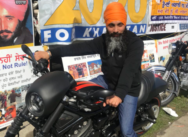 An undated photo of Hapreet Singh Nijjar posing in front of a poster calling for a 2020 referendum on the creation of a separate Sikh state called Khalistan.