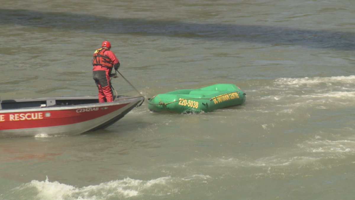 Firefighters retrieve a raft from the Bow River.