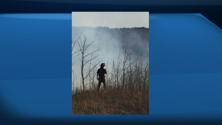 Firefighters monitor a grass fire in Windermere Saturday.