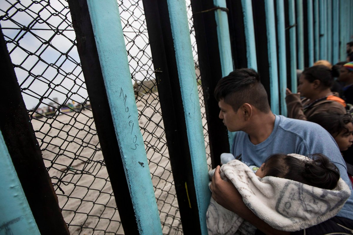 File — In this April 29, 2018 file photo, a member of the Central American migrant caravan, holding a child, looks through the border wall toward a group of people gathered on the U.S. side, as he stands on the beach where the border wall ends in the ocean, in Tijuana, Mexico.