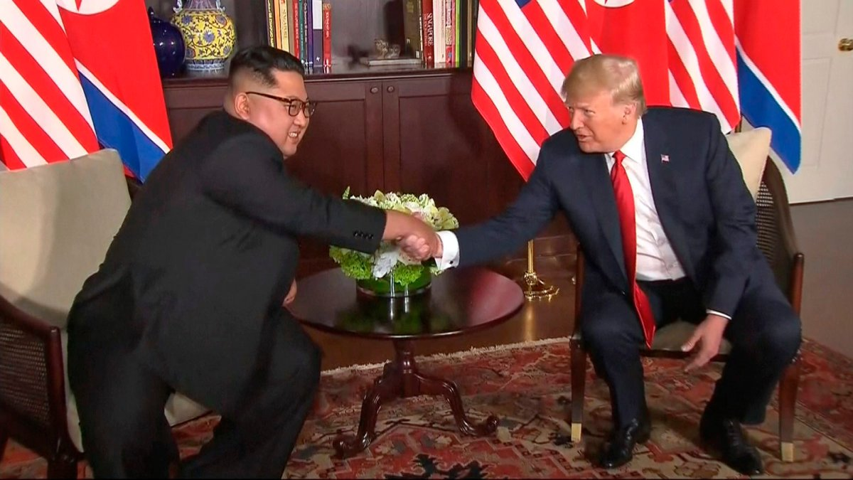 In this image made from video provided by Host Broadcaster Mediacorp Pte Ltd,, U.S. President Donald Trump and North Korean leader Kim Jong Un shake hands ahead of their meeting at Capella Hotel in Singapore, Tuesday, June 12, 2018. (Host Broadcaster Mediacorp Pte Ltd via AP).