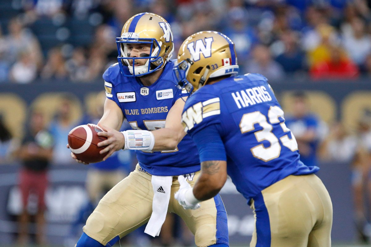 Winnipeg Blue Bombers quarterback Chris Streveler (17) hands off to Andrew Harris (33) against the Edmonton Eskimos during the first half of CFL action in Winnipeg Thursday, June 14, 2018. THE CANADIAN PRESS/John Woods.