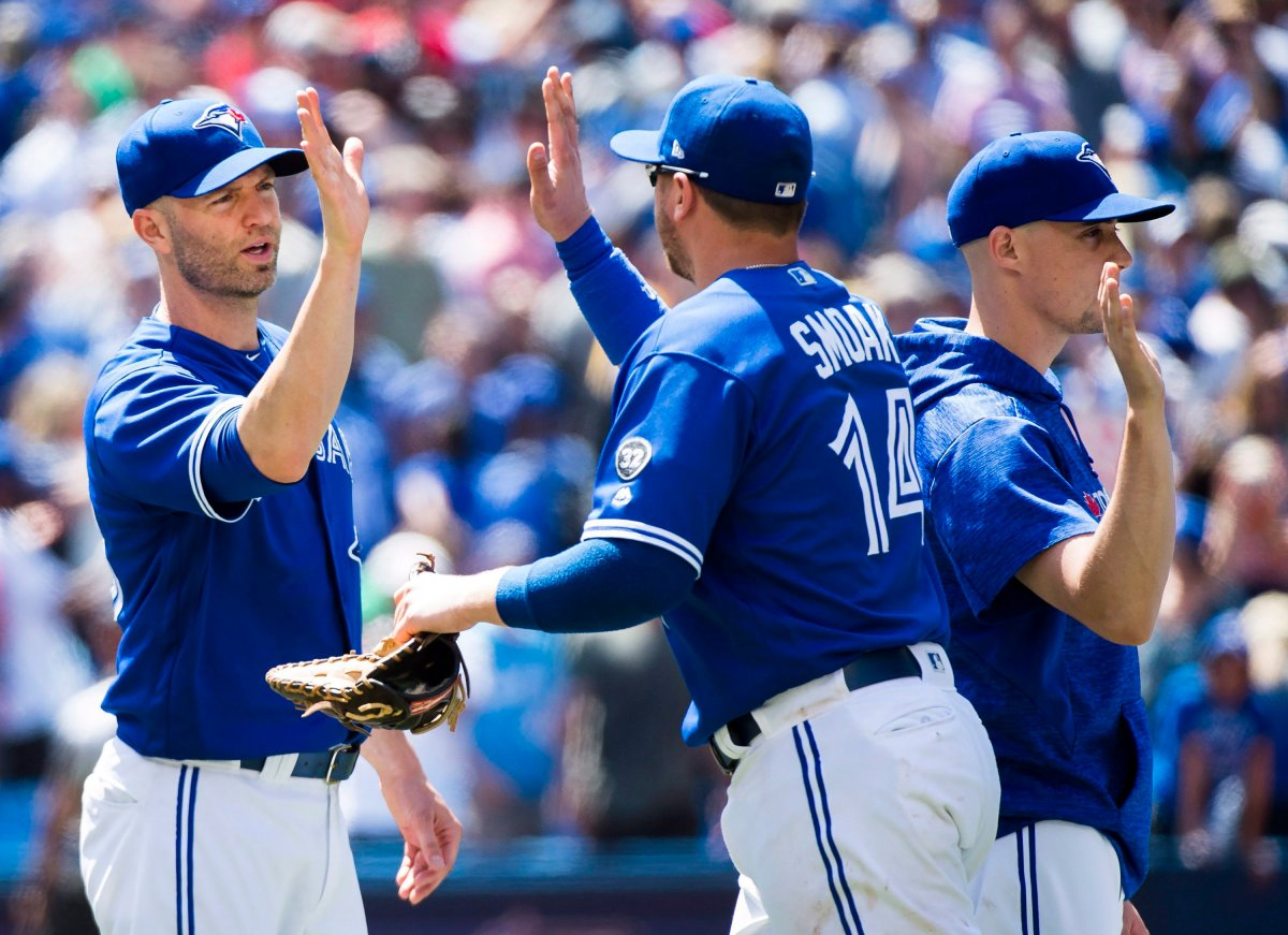 Toronto Blue Jays starting pitcher J.A. Happ, left, celebrates with teammate Justin Smoak (14) after defeating the Atlanta Braves during ninth inning Interleague baseball action in Toronto on Wednesday, June 20, 2018.