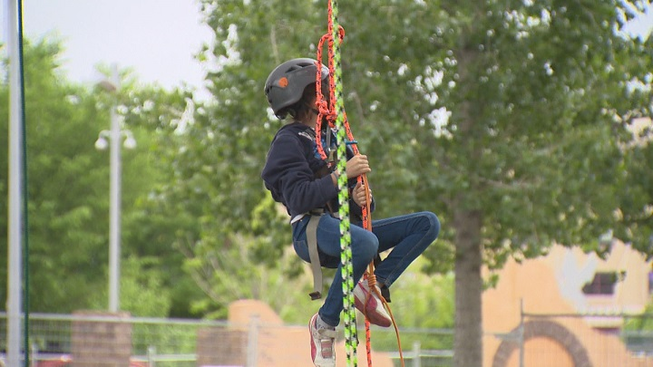 Ten-year-old Marissa Andrade learns how to climb at tree at Arbor Day in Winnipeg.
