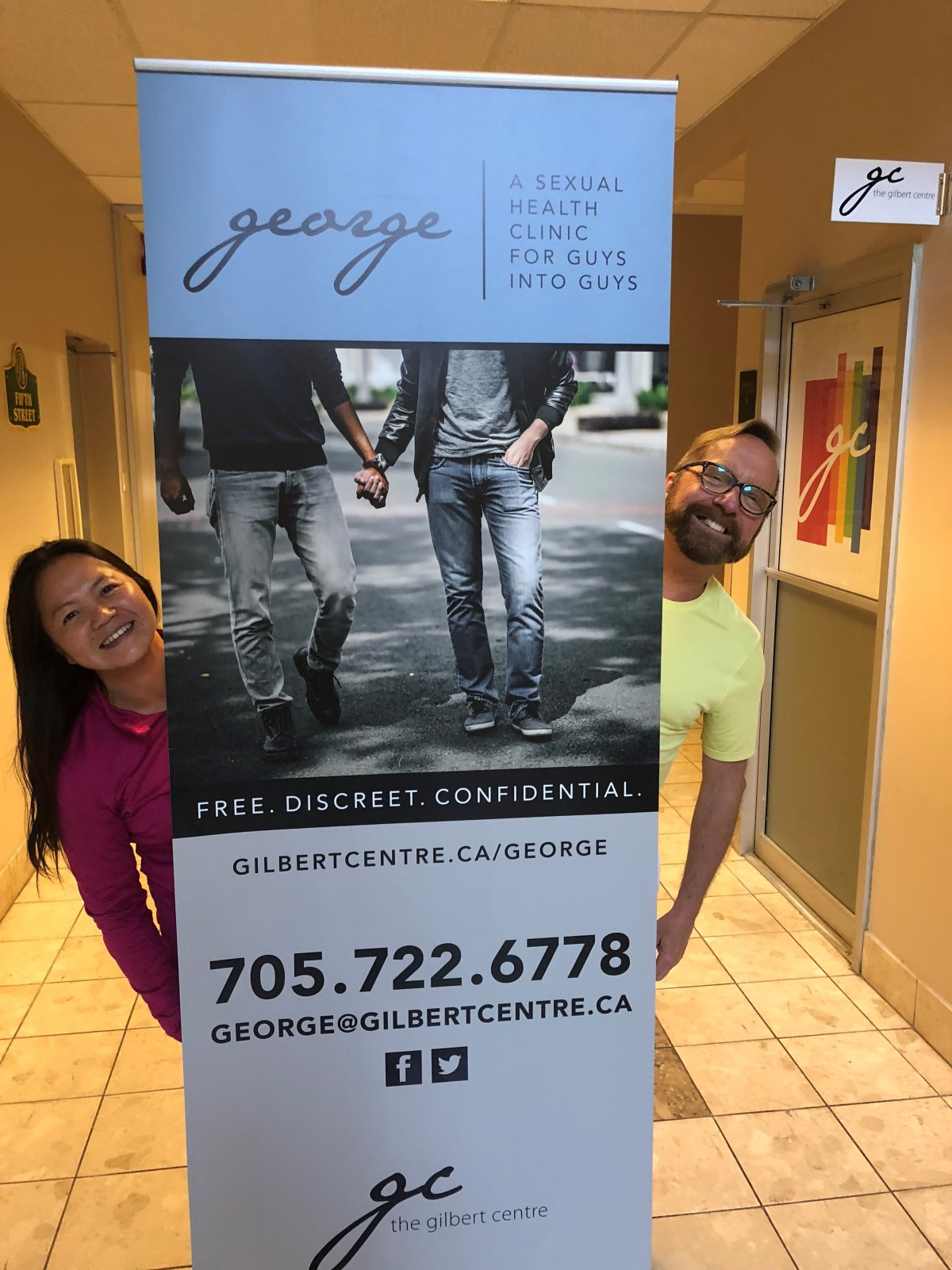 Yen Phan (left) and Gerry Croteau (right) pose with a poster for the new George men's sexual health clinic, set to open June 20.