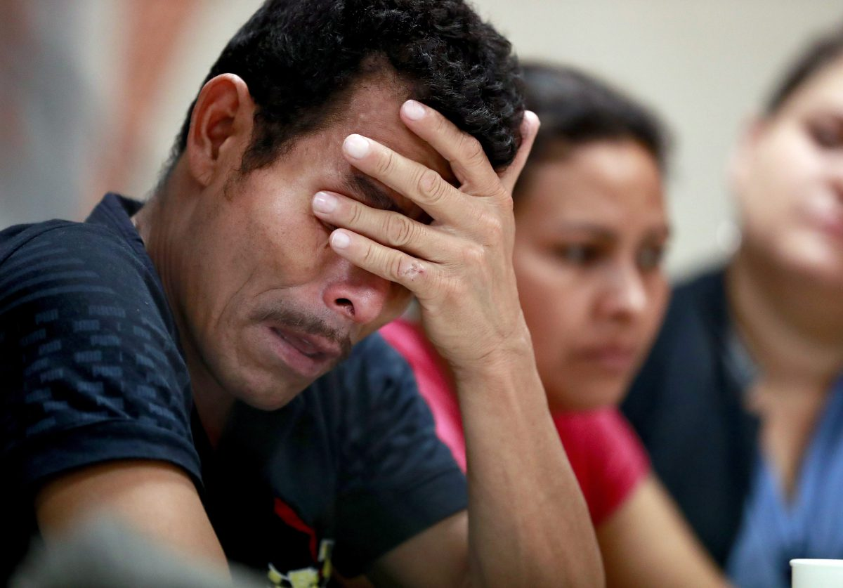 FILE - Melvin, foreground, and Iris, both from Honduras, listen as they hear other immigrants tell of their separation from their children at the border during a news conference at the Annunciation House, Monday, June 25, 2018, in El Paso, Texas.