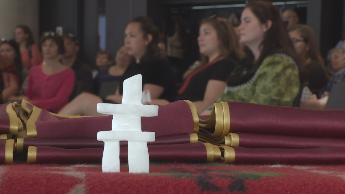 Students did not receive their diplomas but instead were bestowed a red and gold stole which features a white feather.