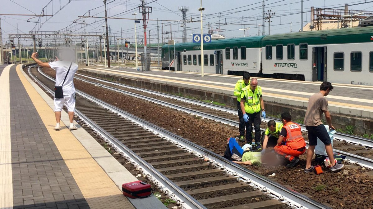 An unknown man takes a selfie as paramedics tend to a Canadian who was hit by a train in Italy.