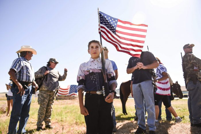 A boy carries a U.S. flag in the barrel of his 20-gauge shotgun before an Independence Day parade in Westcliffe, Colo. on Friday, July 4, 2014.