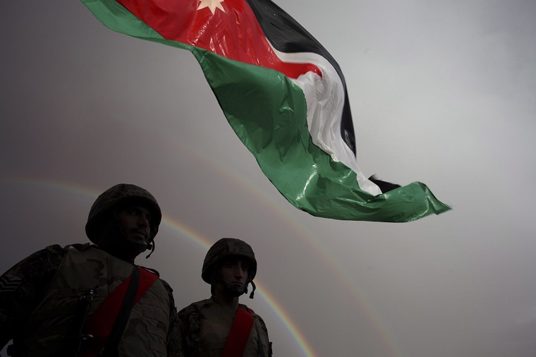 Jordanian border soldiers stand below a Jordanian national flag as the rainbow appears, prior to the arrival of Syrian refugees who will  be crossing into Ruweishid, Jordan, Thursday, Dec. 5, 2013.