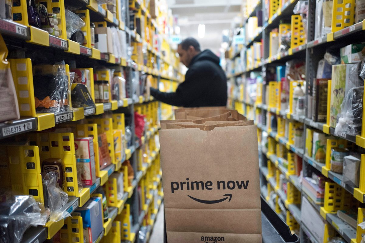 FILE - In this Wednesday, Dec. 20, 2017, file photo, a clerk reaches to a shelf to pick an item for a customer order at the Amazon Prime warehouse, in New York. Amazon announced Thursday, Jan. 18, 2018, that it has narrowed down its potential site for a second headquarters in North America to 20 metropolitan areas, mainly on the East Coast.
