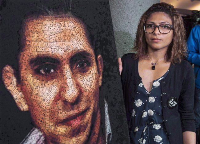 Ensaf Haidar stands next to a poster of a book of articles written by her husband, the imprisoned Saudi blogger Raif Badawi, in Montreal, June 16, 2015.