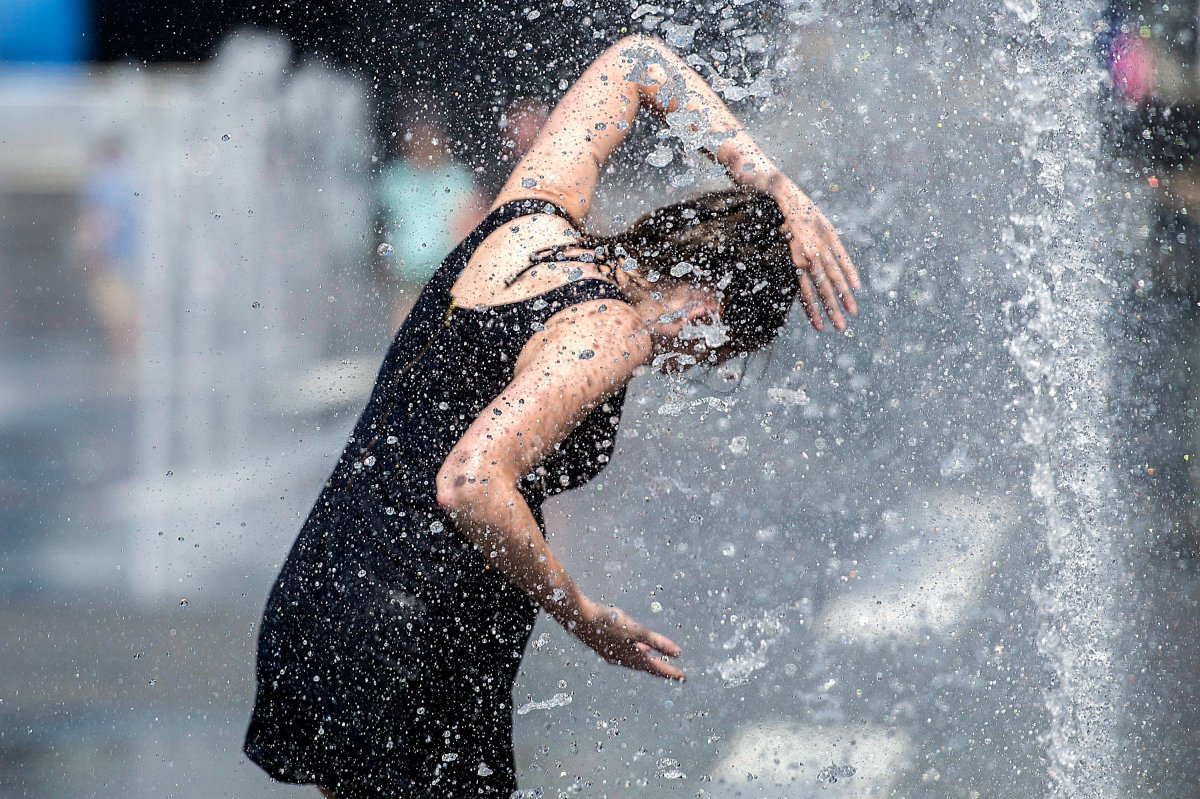 A woman cools down in a water fountain as she beats the heat in Montreal, Monday, July 2, 2018.