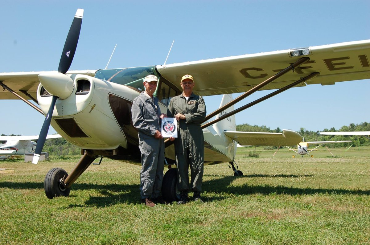 Terry Peters and Oliver Javanpour pose in front of the vintage Stinson 108 aircraft they flew from coast to coast.