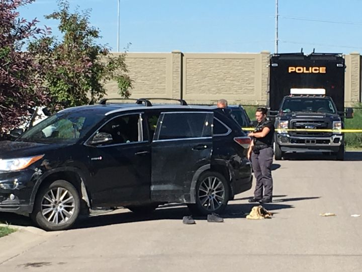 Investigators examine a vehicle in the Auburn Bay area of Calgary following a police shooting on July 12, 2018.