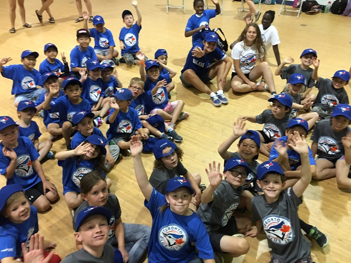 Children dressed in Toronto Blue Jays t-shirts and hats wave during the re-opening of the gym at the Okanagan Boys and Girls Club on Friday. The Blue Jays donated $75,000 to help improve the gym.