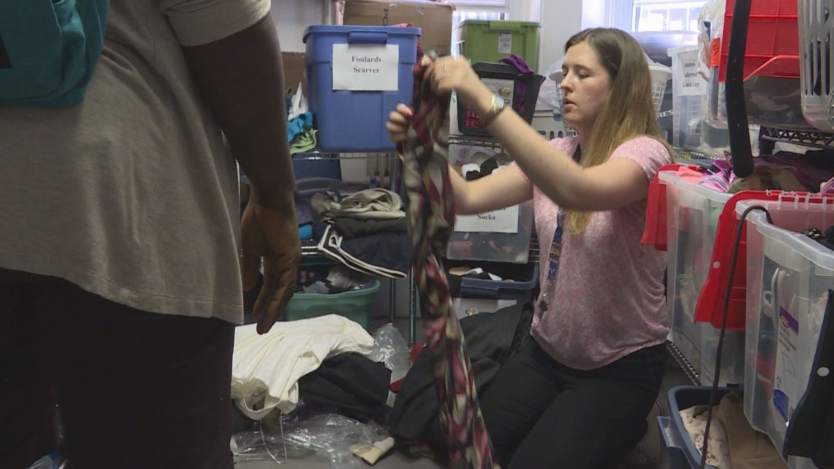 Alannah Gibson, a case worker at Chez Doris, helps sort out donated clothes at the centre.