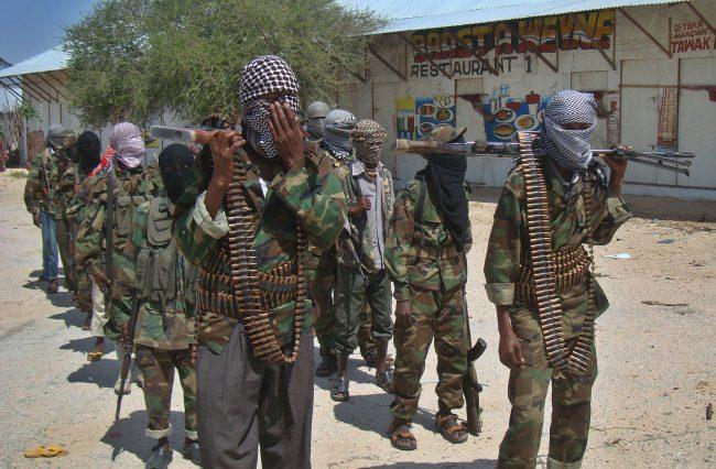"""Al-Shabab recruits walk down a street in the Somali capital Mogadishu on March 5, 2012 following their """"graduation.""""."""
