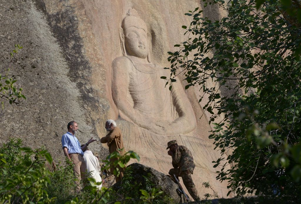 Italian archaeologist Luca Maria Olivieri speaks with Pakistani historian Parvesh Shaheen next to the seventh-century rock sculpture of a seated Buddha carved into a mountain in Jahanabad town in the northwestern Swat Valley of Pakistan, April 26, 2018.
