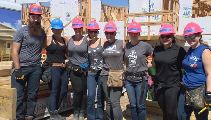 Volunteers from Global Saskatoon roll up their sleeves in a partnership with Habitat for Humanity on Tuesday.