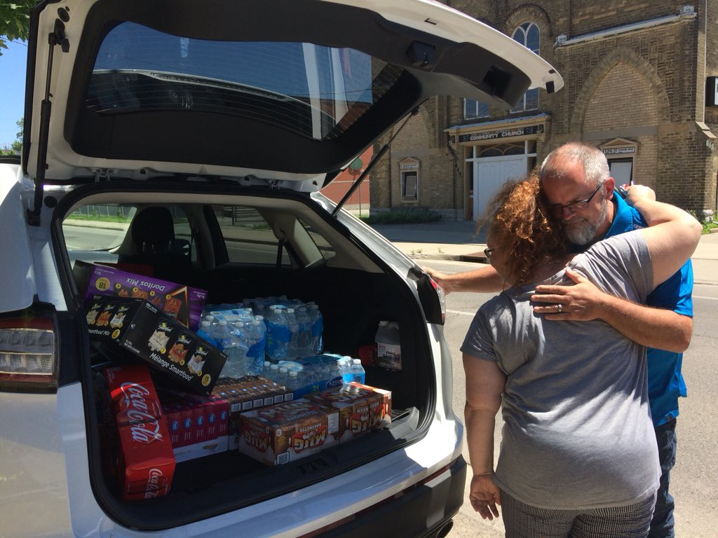 JoDee Durrant-Pheonix gives Bill Norris a hug, after he brings a donation of drinks and snacks for the displaced families.