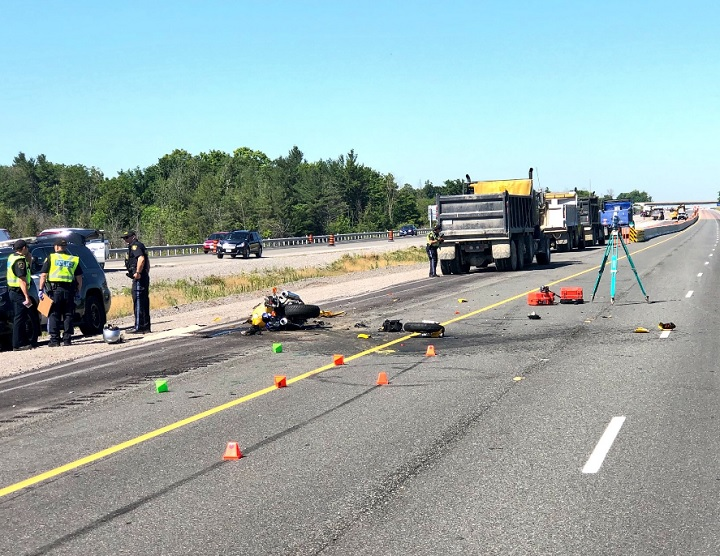 OPP investigate the scene of a fatal crash involving a motorcycle and a dump truck on Highway 407 in Pickering on July 9, 2018.