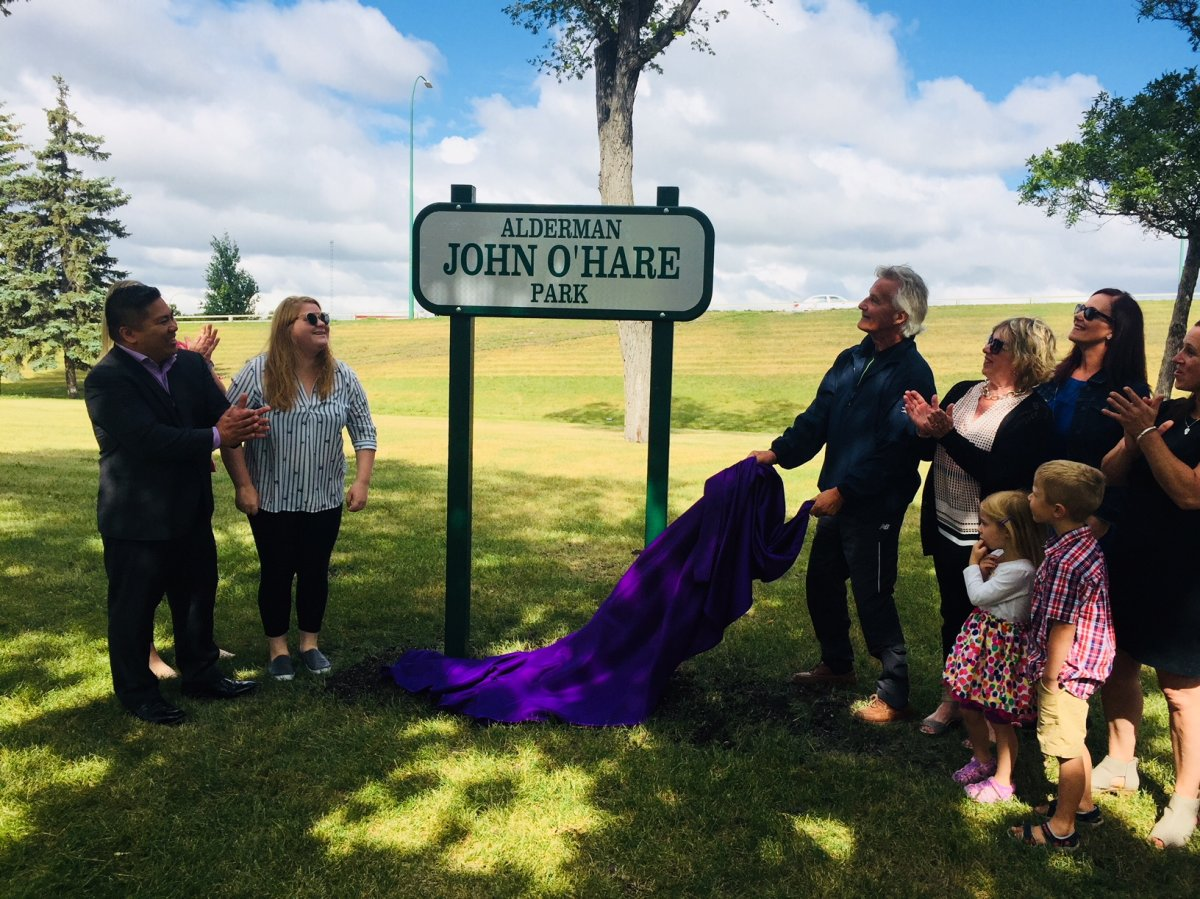 Alderman O'Hare's family members, along with Coun. Mike Pagtakhan (left), show off the park's new sign.