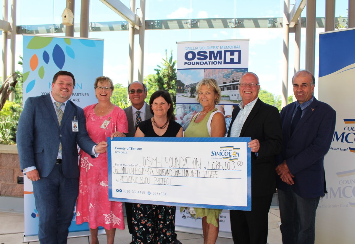 Simcoe County Warden Gerry Marshall presents a $1 million cheque to the Orillia Soldiers' Memorial Hospital July 11.