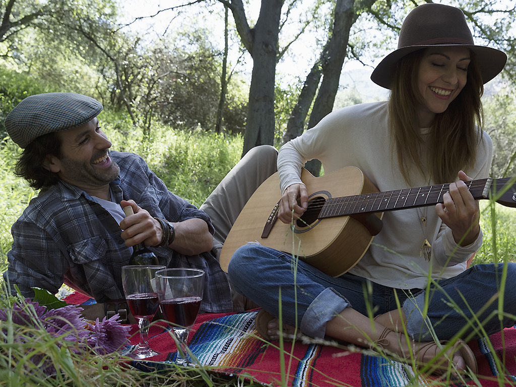 A couple drinks wine in the woods while playing guitar.