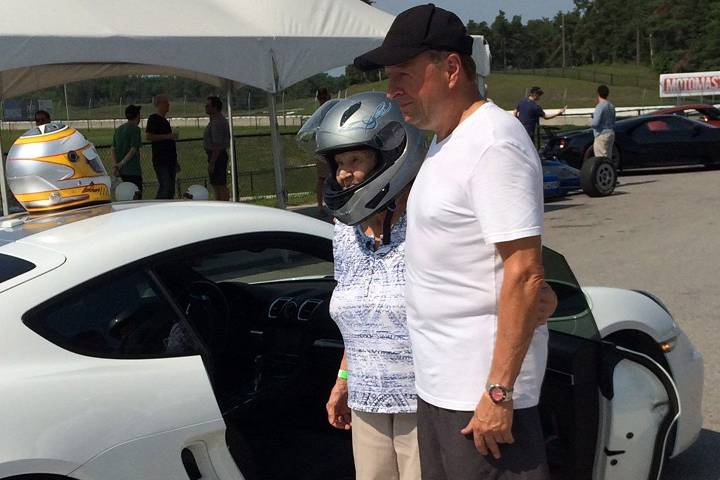90-year-old Maire Hollo poses for a photo with Canadian Motorsport Hall of Fame member Peter Lockhart at the Canadian Tire Motorsport Park in this undated handout photo. A great-grandmother spent her 90th birthday going over 200 kilometres an hour on a racetrack, and she's not slowing down on the fun anytime soon.