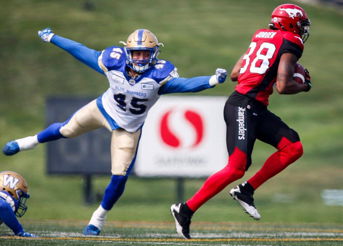 Winnipeg Blue Bombers' Jovan Santos-Knox, left, dives for Calgary Stampeders' Kamar Jorden during first quarter CFL football action in Calgary, Saturday, Aug. 25, 2018. THE CANADIAN PRESS/Jeff McIntosh.