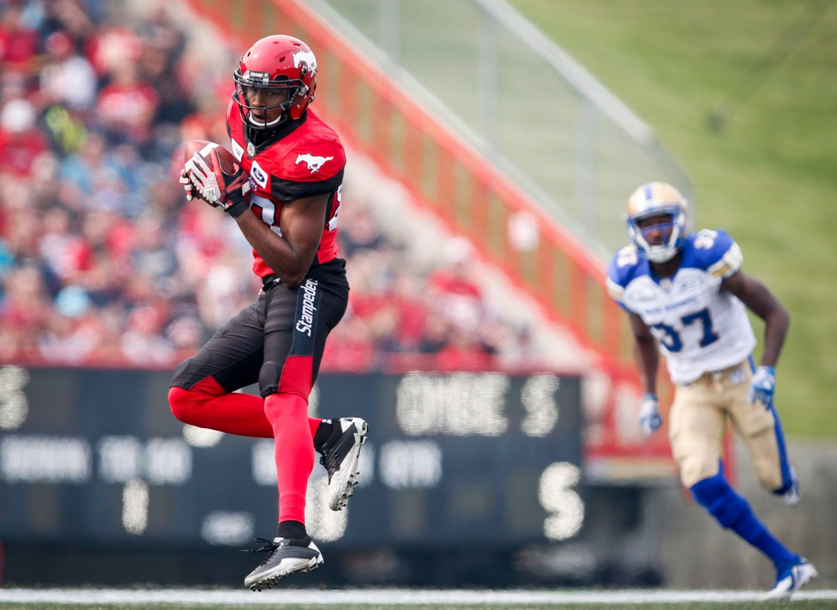 Winnipeg Blue Bombers' Brandon Alexander, right, looks on as Calgary Stampeders' Kamar Jorden catchess a pass during second half CFL football action in Calgary, Saturday, Aug. 25, 2018.