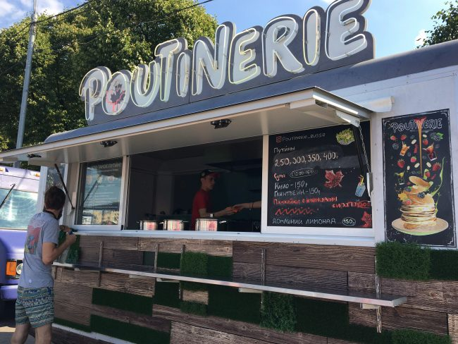 """Owners Masha Klimova and Alexey Kolesov's """"Poutinerie"""" food truck is being prepared for the day at the Faces & Laces Festival in Gorky Park, Moscow, Russia, Aug. 18, 2018."""