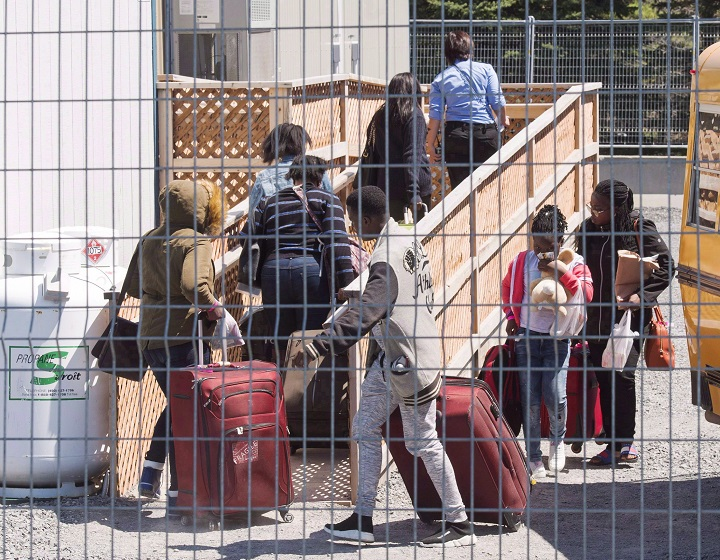 A group of asylum seekers arrive at the temporary housing facilities at the border crossing Wednesday May 9, 2018 in St. Bernard-de-Lacolle, Quebec.
