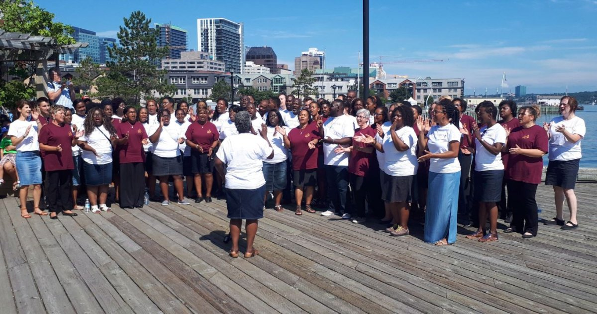 Karen Burke (foreground), director of Toronto Mass Choir, and singers from the Nova Scotia Mass Choir and the Toronto Mass Choir, are shown in Halifax, Saturday, Aug.4, 2018 Two award-winning Canadian gospel choirs wowed unsuspecting pedestrians on a busy waterfront Saturday morning with an impromptu performance.