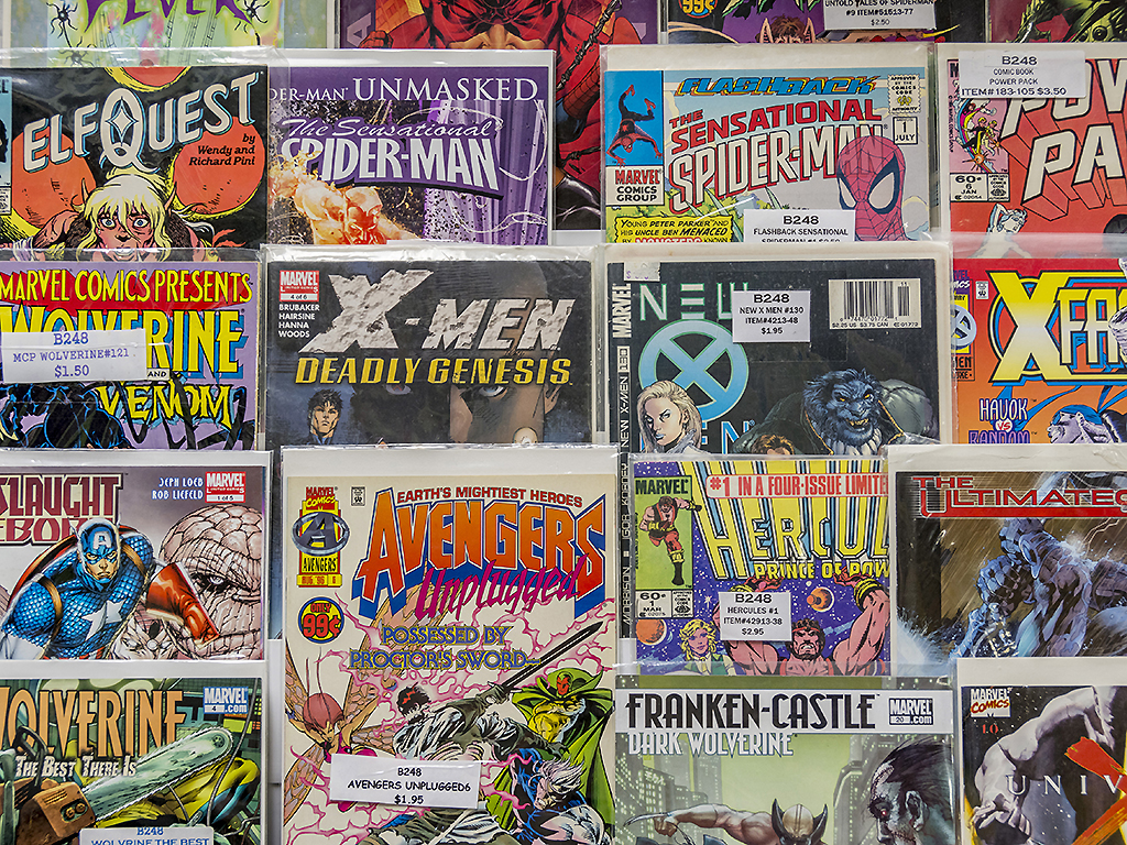 A rack of comic books for sale at a flea market.
