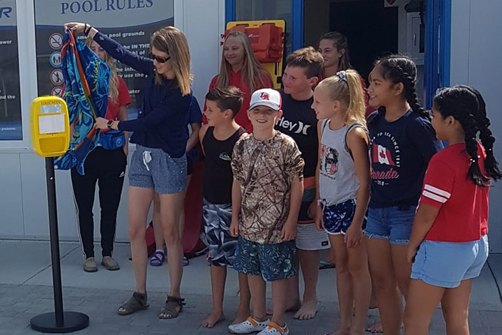 Meagan Greene and her Grade 4 students at the unveiling of a free sunscreen dispenser at the Panther Swimming Pool in Davidson, Sask.