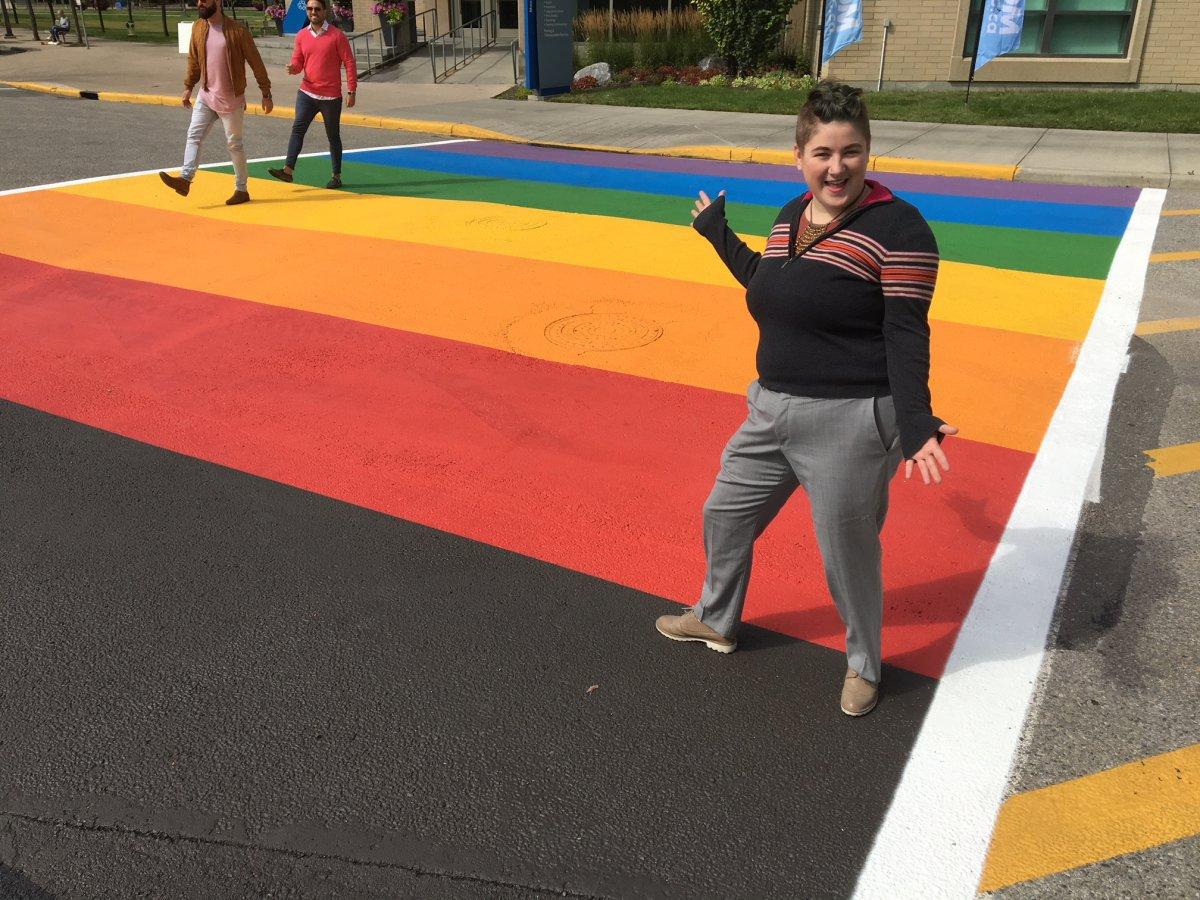 MRU student Eddy Robinson stands on the new, permanent rainbow crosswalk on the campus.