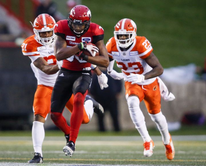 BC Lions' Otha Foster III, left, and Anthony Thompson, right, chase Calgary Stampeders' Kamar Jorden, during second half CFL football action in Calgary, Saturday, Aug. 4, 2018.