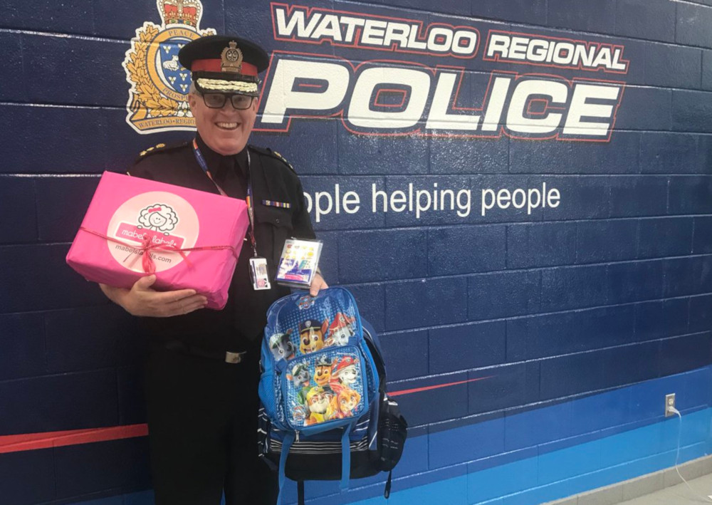 Waterloo police Chief Bryan Larkin with a couple of the more-than-1,400 backpacks that were donated.