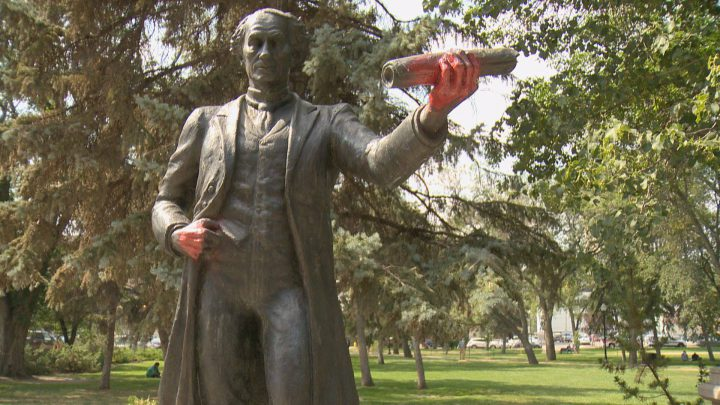 The John A Macdonald statue in Regina's Victoria Park with spray-painted red hands.