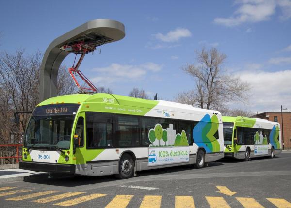 File photo of two quick-charging electric buses operating in Montreal, with a charging station above.