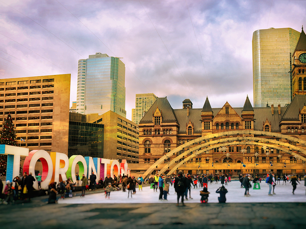 Lots of people are having fun by the colourful Toronto sign at Nathan Phillips Square.
